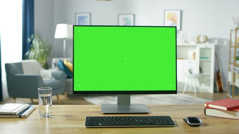 Zoom in On a Modern Personal Computer with Mock-up Green Screen Display Standing on the Desk of the Cozy Home Office. Living Room Created by Interior Designer with Good Taste and Style.