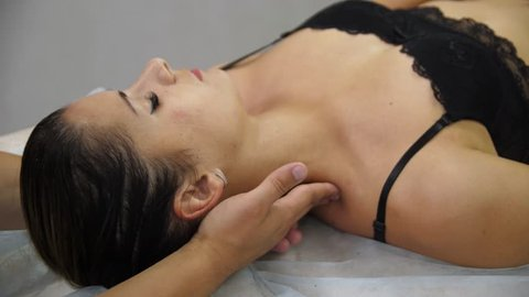 Woman doing neck massage at the reception of the chiropractor. Men's hands do massage of the cervical spine to an attractive girl. Massaging pain points. A grimace of pain.