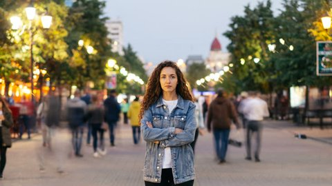 Time-lapse of good-looking woman towny in denim clothing standing alone in the street among crowds of people and looking at camera. Street lights are visible.
