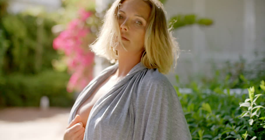 Blond Woman Wearing Open Grey Robe Revealing Bare Skin Beneath Looking  Startled or Surprised at the Camera in Back Yard Garden 8854f735d