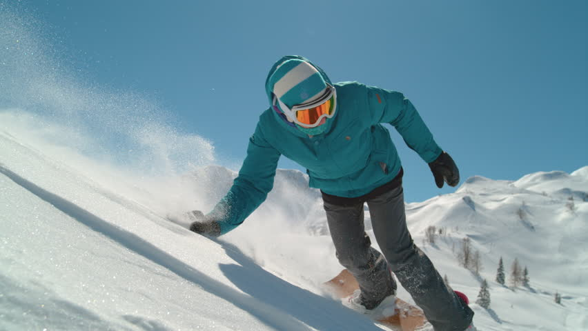 SLOW MOTION CLOSEUP Smiling girl snowboarding in mountains on sunny winter day. Freeride snowboarder riding powder snow past the camera, doing hand drag on fresh snow surface. Woman backcountry skiing