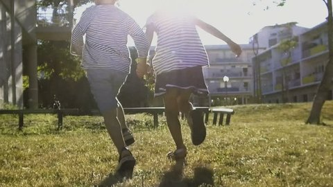 Kids holding hands and running in summer with sunlight. Rear view of children having fun on lawn. Slow motion. Girl jumping over obstacle on playground. Childhood concept