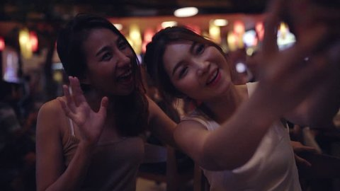 Slow motion - Backpacker Asian women lesbian lgbt couple taking selfie drinking alcohol or beer with friend and party at Khao San Road in Bangkok, Thailand. Lifestyle women party with friends concept.