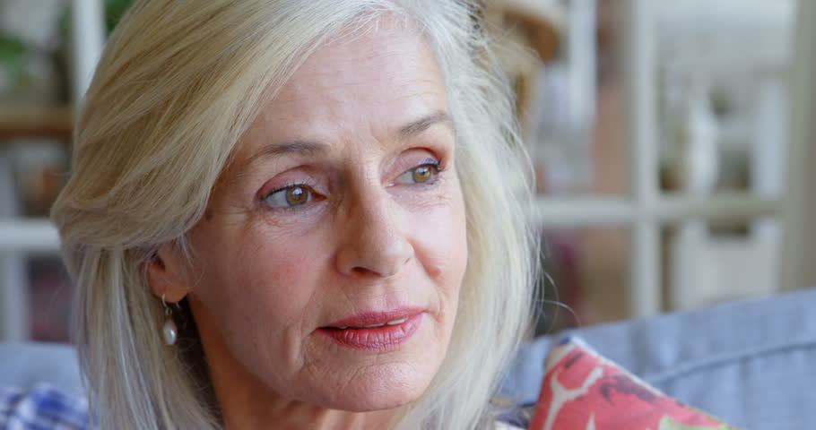 Close-up of thoughtful Caucasian senior woman sitting on sofa at home  | Shutterstock HD Video #1016449363