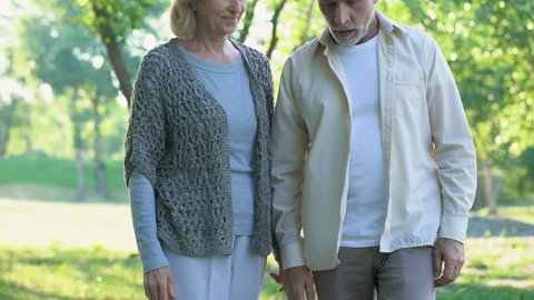 Aged man having heart pain during walk with wife, heart attack, healthcare