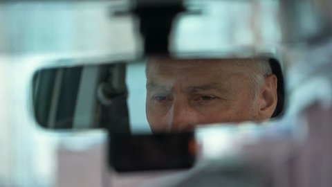 Elderly man wearing hat and looking in rear view car mirror, driver close-up