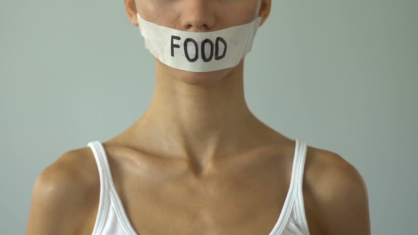 Girl with taped mouth holding empty plate, food restriction causes anorexia