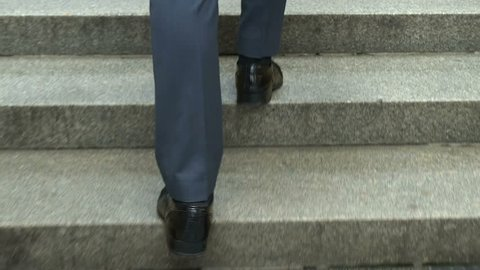 Man in suit walking upstairs, concept of successful career, achievements closeup