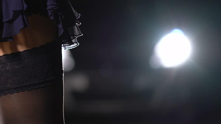 Seductive woman giving start sign to night street racing cars, smoking cigarette