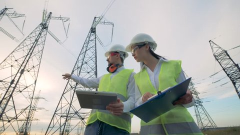 Engineers work with a tablet on power lines. Power lines, power substation, electrical substation, electric substation concept.
