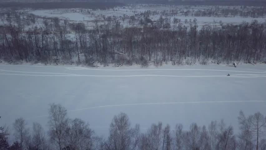 The Udege hunter rides a snowmobile on the frozen Bikin River for hunting.   Shutterstock HD Video #1016479423