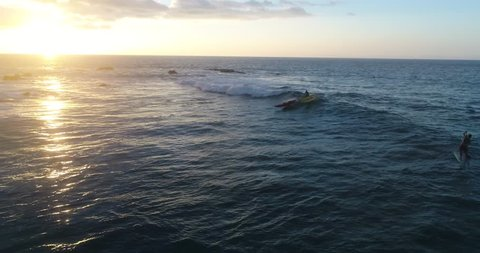Slow motion aerial footage of a man canoe surfing a fun wave at sunset in Kailua Kona, Hawaii