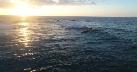 Aerial footage of a man canoe surfing a fun wave at sunset in Kailua Kona, Hawaii