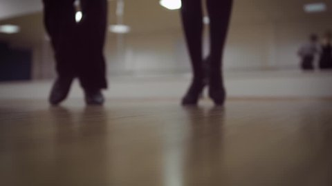 Dancing male and female legs in the dance studio
