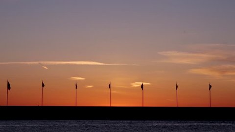 Flags waving in the sunset in Helsingborg, Sweden. Bird flying by in the background.