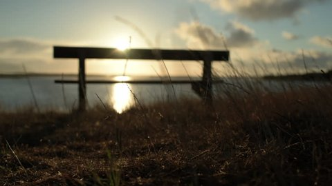 Cameraing towards a bench by the beach at sunrise in Hengistbury in Dorset
