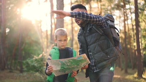 Slow motion of little boy holding map standing in forest while his father is talking and gesturing teaching his son orientation in wood. Nature, family and navigation concept.