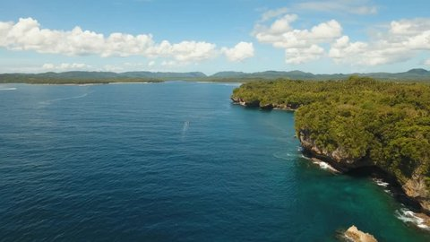 aerial footage rocky coast, surf, waves breaking about stones Seascape of the coast, palm trees, sea. Siargao, Philippines