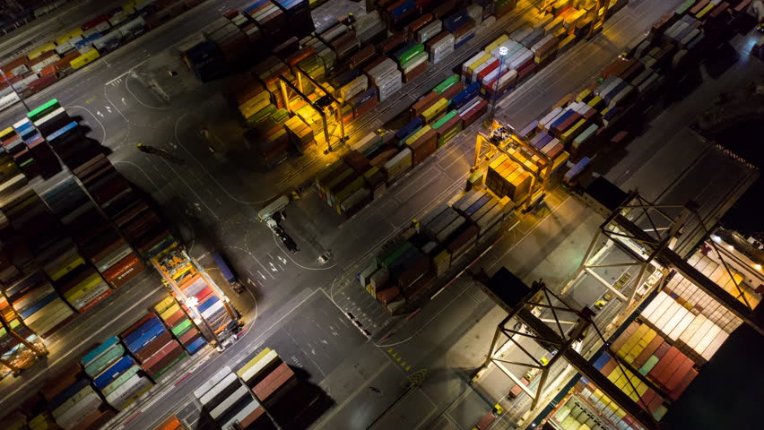 Aerial hyperlapse - Night shot of busy port. Shipping containers being transported with lifting cranes and network trucks to their final destination