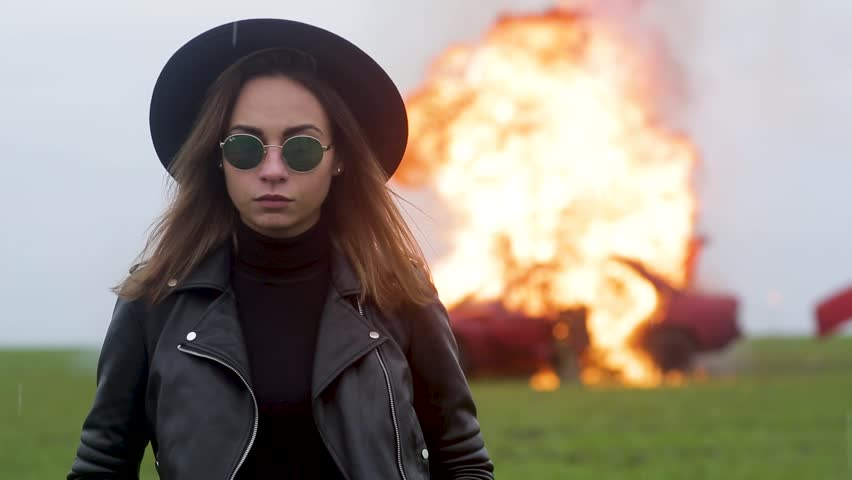 Stylish model against the background of an exploding car, girl and exploding car