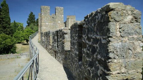 POV on allure or Wall-walk in Tomar Fortress, Portugal, Unesco Heritage. Tomar convent-fortress was part of a defensive system created by Knights of Hordes of the Templars. Summer season, blue sky.