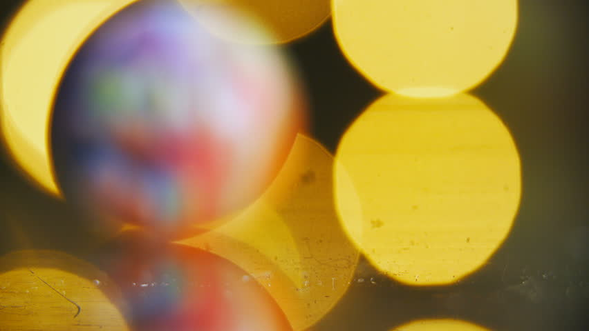Planet shaped colorful marble roll towards the camera macro shot 4K. Long shot with shallow depth of field with a ball passing over being in focus for a second. Background light out of focus.