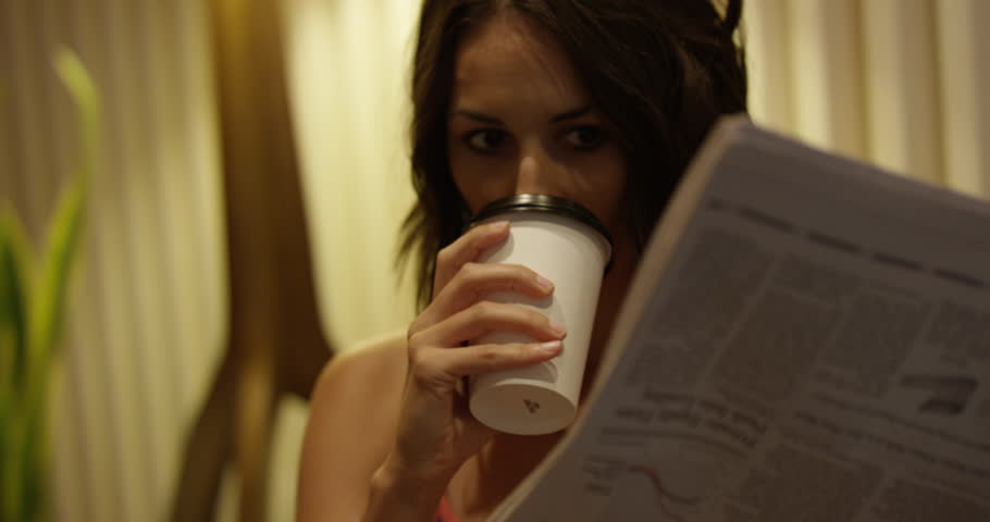 Young hip woman reads news paper while drinking coffee - morning routine - straight on shot | Shutterstock HD Video #1016592073