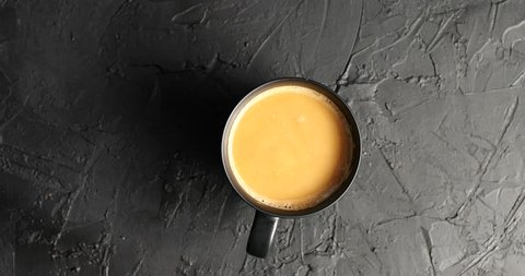 Top view of round brown mug filled with coffee and milk on top of textured gray surface