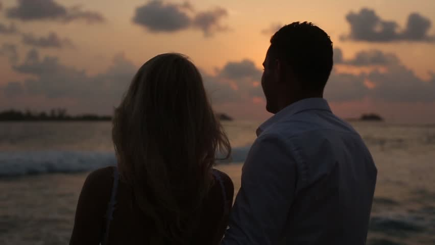 Back view of bride and groom enjoying sunset on tropical beach near balustrade on vacation. Newlyweds hugging and watching ocean after ceremony on honeymoon. Tropical wedding at Maldives luxury spa
