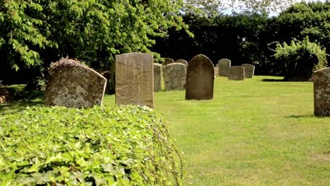 Headstones in a churchyard with ivy-covered table tomb POV SHOT