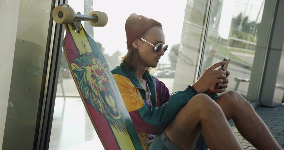 Laughing young man dressed like a hipster in round glasses sits with his skateboard on the floor and watches funny video on his smartphone
