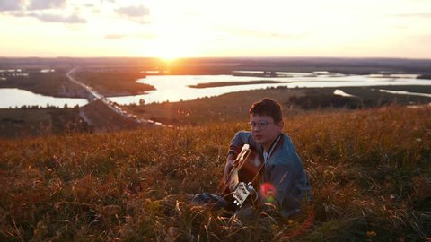 Boy in round glasses playing guitar in field in sunset and looking to the sky
