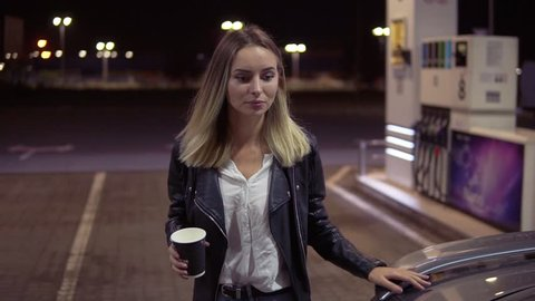 Blonde young woman open the car door while holding a cup of coffee and sits on a passenger seat. Petrol station. Night