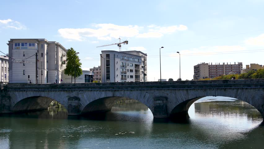 A tram passes through Le Mans, on a bridge over the Sarthe River. In 2015, the city had 143,325 inhabitants, making it the largest city in the Sarthe, the third largest city in the Pays de la Loire. | Shutterstock HD Video #1016670613