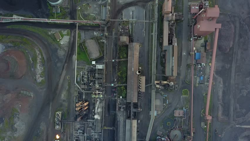 Aerial drone footage of an industrial steel plant at night.  Smoke billows out of towers and complex piping covers the ground. | Shutterstock HD Video #1016686423