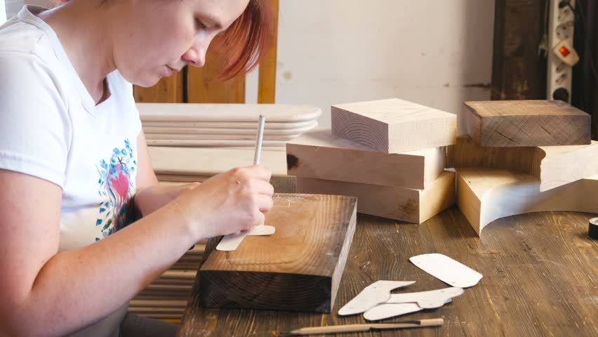 Woman repaints the paper stencil to the wooden bar.