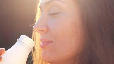Woman drinking a milk drink - milk, kefir, yoghurt. Close-up portrait of a girl face