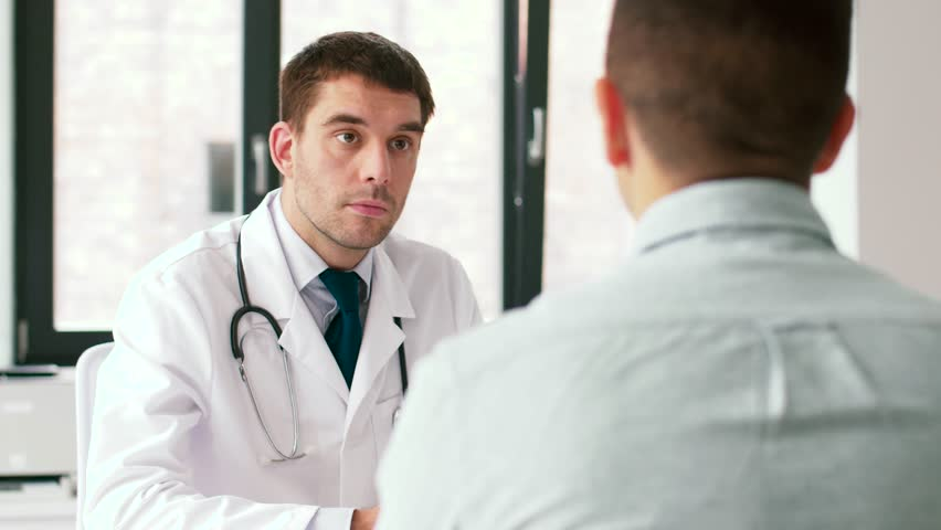 Medicine, healthcare and people concept - doctor and male patient having health problem meeting at hospital   Shutterstock HD Video #1016808403