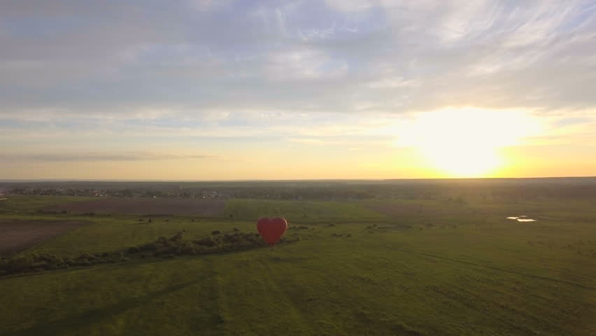 Red balloon in the shape of a heart.Aerial view:Hot air balloon in the sky over a field in the countryside in the beautiful sky and sunset.