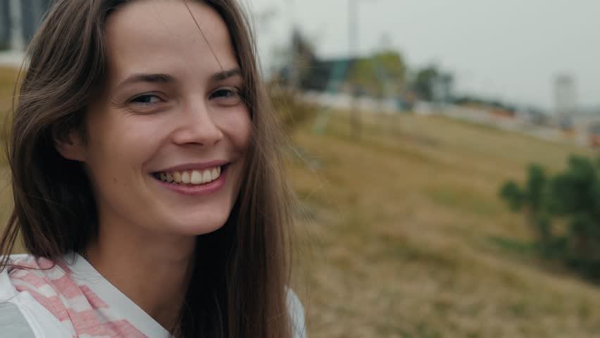 Happy woman with perfect smile looking at camera outdoors in the street student happy laughing smiling young   Shutterstock HD Video #1016828713