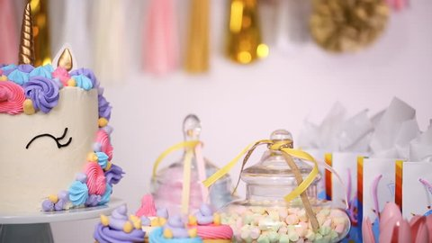 Close up of little girl's birthday party table with unicorn cake, cupcakes, and sugar cookies.