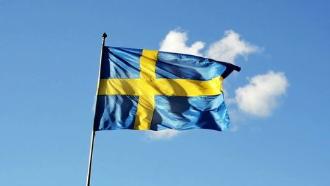 Swedish flag in slow motion against blue sky