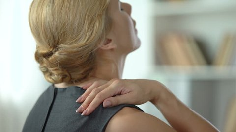 Overworked woman feeling strong shoulder pain, nerve inflammation, back view