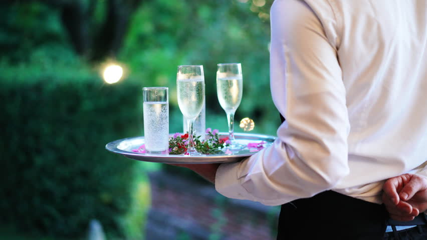 Waiter and champagne glasses on a tray in Luxury Restaurant. Catering service. 4k | Shutterstock HD Video #1016867023