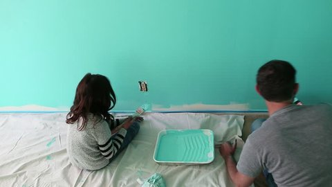 Handheld shot of father and daughter painting wall at home