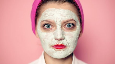 Close-up of a girl with a mask on her face and a towel on her head with a wide-open eyes smiling. Beautiful girl with cosmetic mask on her face. Woman wearing face mask. Face care concept