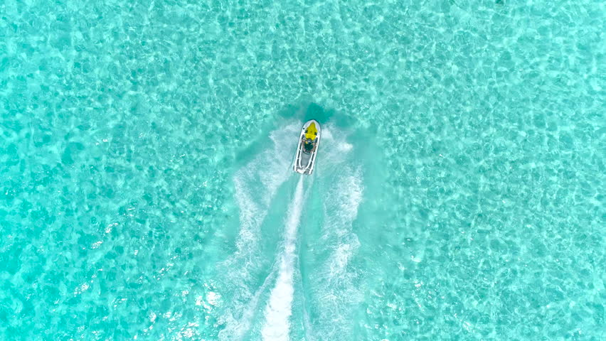 Aerial - Top view of  jet ski racing on a crystal clear water. Adult male enjoying summer vacation in Bora Bora on a jet ski