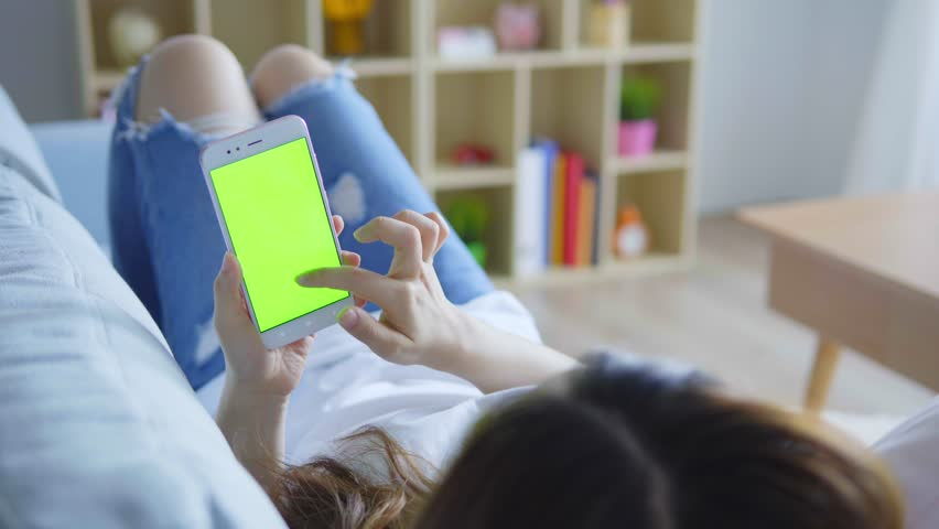 Woman In White Top Laying On Sofa Uses Smartphone With Green Screen | Shutterstock HD Video #1016927773