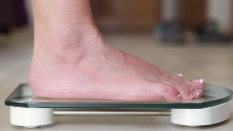Adult woman measuring her weight with weight scale. Close up side view video shooted from floor point.