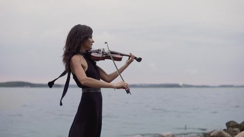 Beautiful girl in long black dress plays violin at sea background. Young girl with violin. Art concept in 4k with copy space at right. Medium shot